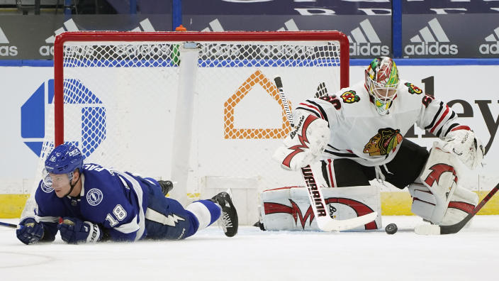 Chicago Blackhawks goaltender Collin Delia (60) makes a save after Tampa Bay Lightning left wing Ondrej Palat (18) fell down during the first period of an NHL hockey game Friday, Jan. 15, 2021, in Tampa, Fla. (AP Photo/Chris O'Meara)