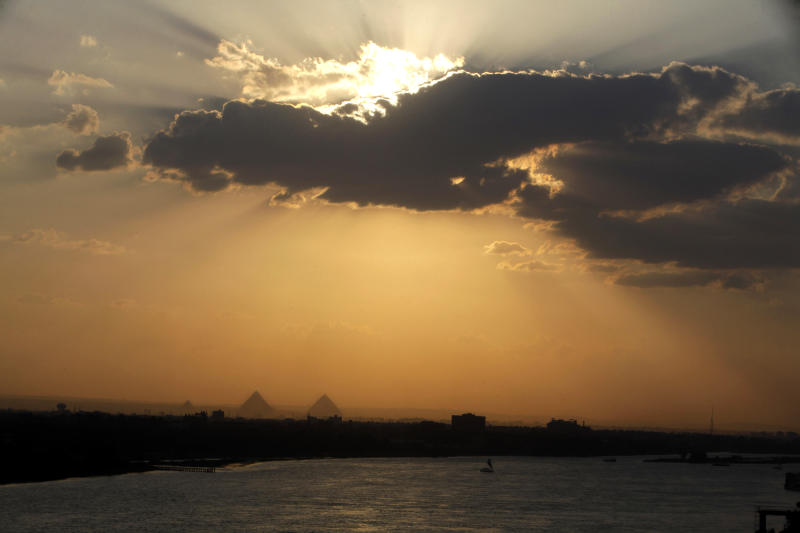 The sun sets over the Nile River and the historical site of the Giza Pyramids as seen from Cairo, Egypt, Tuesday, May 21, 2013.  Egypt's president has signed a new tax law that cuts the amount paid by poorer Egyptians while increasing taxes on small and medium-sized businesses. The measure is among many economic reforms the government is trying to impose to control its burgeoning budget deficit. Egypt is negotiating a $4.8 billion loan from the International Monetary Fund, which is pushing for economic revisions.(AP Photo/Amr Nabil)