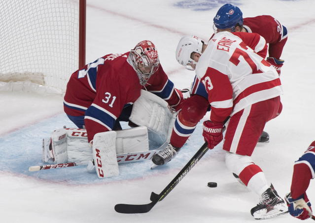 Detroit Red Wings' Adam Erne (73) moves in against Montreal Canadiens goaltender Carey Price (31) as Canadiens' Christian Folin (32) defends during second-period NHL hockey game action in Montreal, Thursday, Oct. 10, 2019. (Graham Hughes/The Canadian Press via AP)