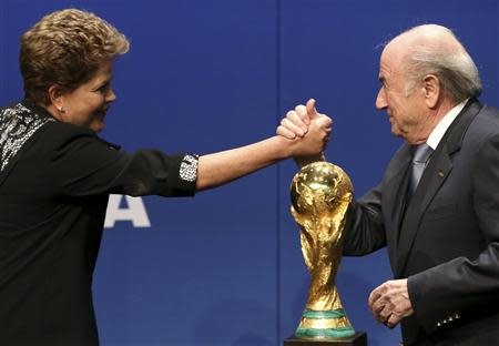 Brazil's President Dilma Rousseff (L) shakes hands with FIFA President Sepp Blatter after delivering a statement at the FIFA headquarters in Zurich January 23, 2014. REUTERS/Thomas Hodel