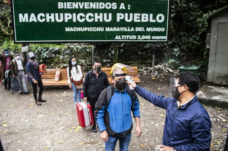 Visitors to the hamlet of Machu Picchu, also known as Aguas Calientes, get their temperature before they can visit the Inca ruins