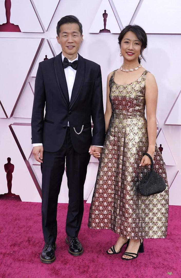 Lee Isaac Chung in a dark suit and Valerie Chung in a metallic ankle-length dress