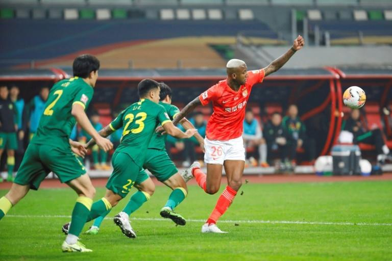 Guangzhou Evergrande's Talisca (red shirt) against Beijing Guoan players during their Chinese Super League football match