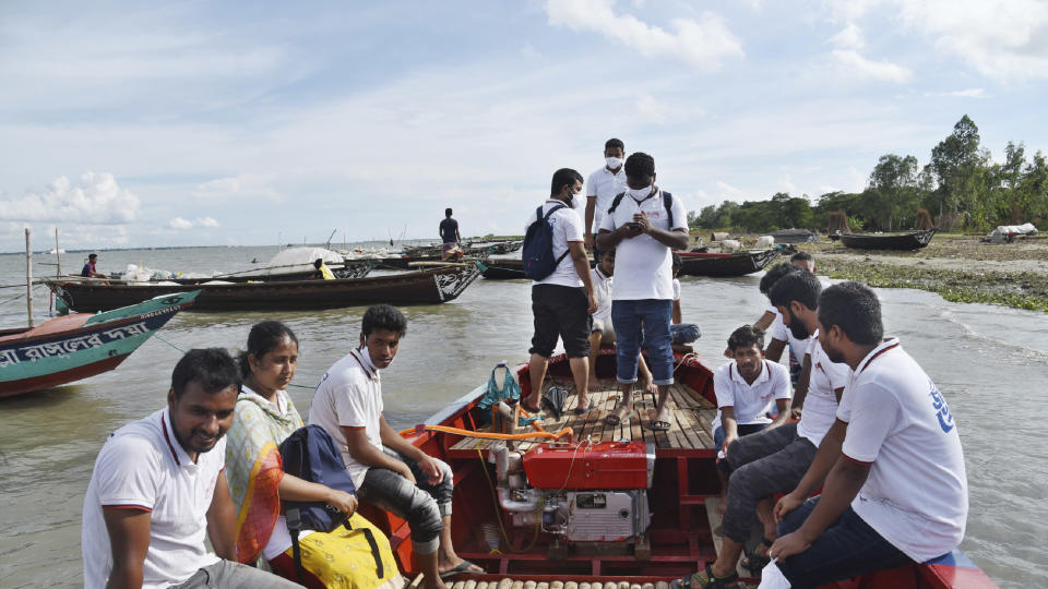 In this photo provided by Bidyanondo Foundation, doctors and health workers arrive at a village in Chandpur district in eastern Bangladesh, on Sept. 12, 2020. A Bangladeshi charity has set up a floating hospital turning a small tourist boat into a healthcare facility to provide services to thousands of people affected by this year's devastating floods that marooned millions. (Bidyanondo Foundation via AP)