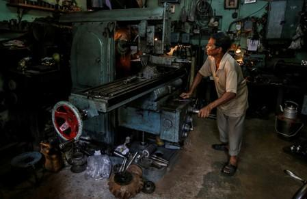 FILE PHOTO: A worker operates a lathe as he makes spare parts of car gearboxes at a workshop in Kolkata