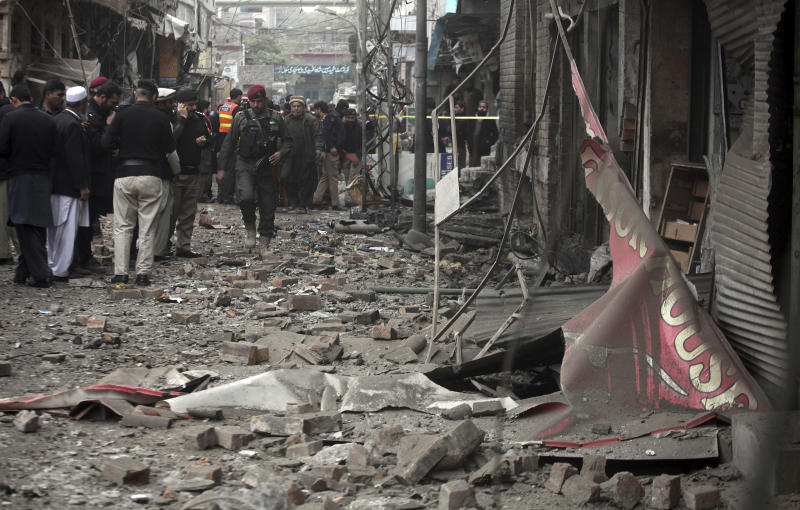 Pakistani police officers examine the site of bomb blast in Peshawar, Pakistan, Saturday, Jan. 5, 2019. Pakistani police say a car bomb exploded in a Peshawar neighborhood wounding three people and damaging several shops. (AP Photo/Mohammad Sajjad)