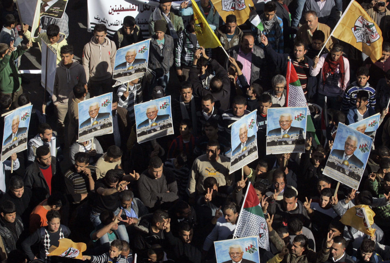 Palestinians hold pictures of President Mahmoud Abbas and wave Fatah flags during a rally supporting the Palestinian UN bid for observer state status, in the West Bank city of Nablus, Thursday, Nov. 29, 2012. The Palestinians are certain to win U.N. recognition as a state on Thursday but success could exact a high price: delaying an independent state of Palestine because of Israel's vehement opposition. (AP Photo/Nasser Ishtayeh)