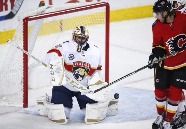 Florida Panthers goalie Roberto Luongo, left, deflects the puck on a shot from Calgary Flames' Elias Lindholm, of Sweden, during first-period NHL hockey game action in Calgary, Alberta, Friday, Jan. 11, 2019. (Jeff McIntosh/The Canadian Press via AP)