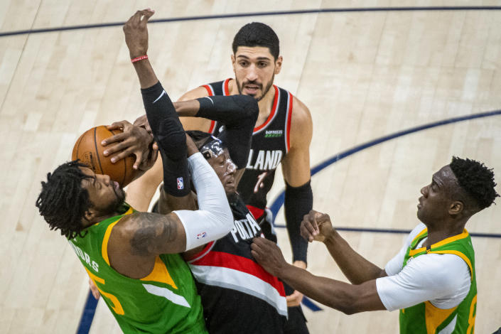 Portland Trail Blazers forward Robert Covington, center, and Utah Jazz center Derrick Favors, left, compete for possession of the ball during the first half of an NBA basketball game Thursday, April 8, 2021, in Salt Lake City. (AP Photo/Isaac Hale)