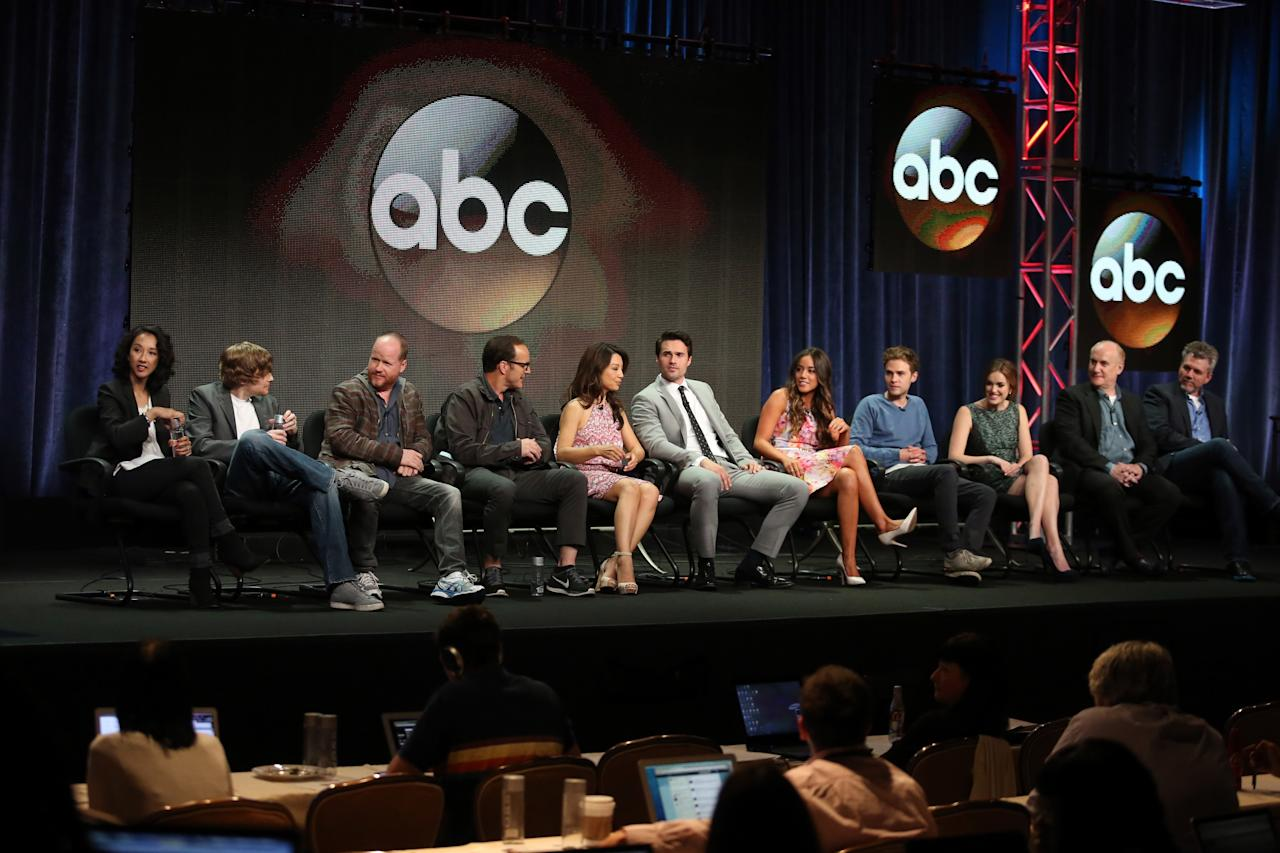 "BEVERLY HILLS, CA - AUGUST 04: (L-R) Executive producers Maurissa Tancharoen, Jed Whedon, Joss Whedon, actors Clark Gregg, Ming-Na Wen, Brett Dalton, Chloe Bennet, Iain De Caestecker, Elizabeth Henstridge, executive producers Jeph Loeb, and Jeffrey Bell speak onstage during the ""Agents of S.H.I.E.L.D."" panel discussion at the Disney/ABC Television Group portion of the Television Critics Association Summer Press Tour at the Beverly Hilton Hotel on August 4, 2013 in Beverly Hills, California. (Photo by Frederick M. Brown/Getty Images)"