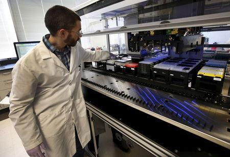 Technician Matthew Smith loads a robotic DNA sample automation machine at a Regeneron Pharmaceuticals Inc. laboratory at the biotechnology company's headquarters in Tarrytown, New York March 24, 2015. REUTERS/Mike Segar
