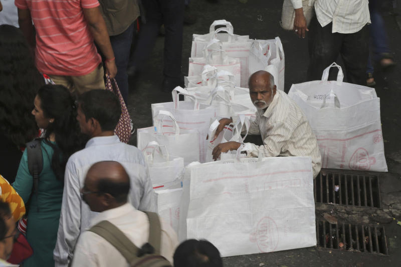 FILE - In this July 5, 2019, file photo, a street vendor wait to sell bags outside a railway station in Mumbai, India. Asian shares advanced Friday, Sept. 20, 2019, and India's benchmark jumped 5.4% after the government announced plans to cut corporate taxes. (AP Photo/Rafiq Maqbool, File)