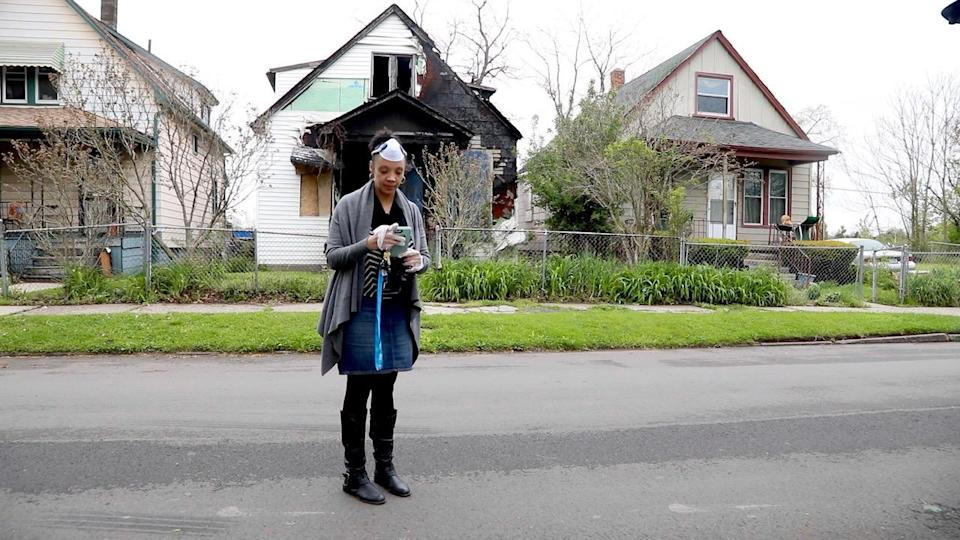 Principal Jacqueline Dungey checks her phone after knocking on a family's door a few blocks from her school and learning that the family had moved. (Jake Whitman / NBC News)