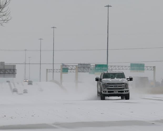 A pickup truck and other vehicles are seen making their way along a snow-covered stretch of Interstate 10 on Monday in Houston.
