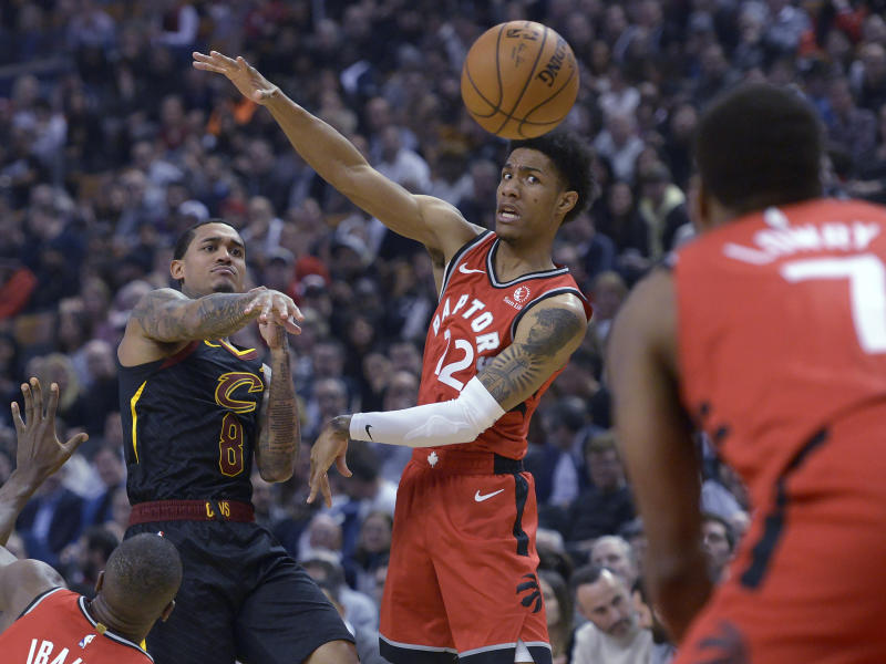 Cleveland Cavaliers guard Jordan Clarkson (8) passes the ball past Toronto Raptors forward Oshae Brissett (12) during first half NBA basketball action in Toronto on Monday, Dec. 16, 2019. (Nathan Denette/The Canadian Press via AP)