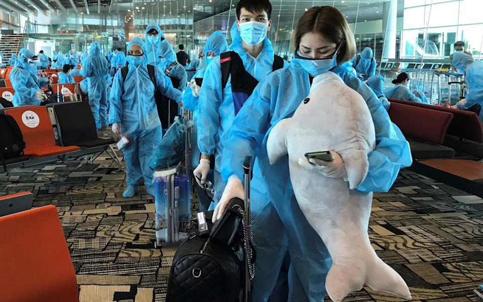 A Vietnamese woman carries a stuffed animal while boarding a repatriation flight from Singapore to Vietnam amid spread of the coronavirus outbreak - REUTERS/Mai Nguyen