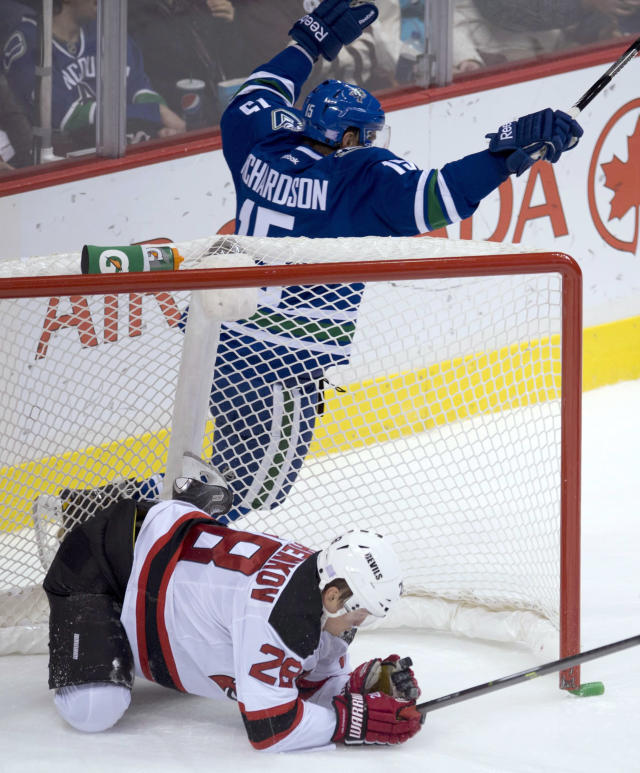 Vancouver Canucks defenseman Jason Garrison (5) skates past as New Jersey Devils defenseman Anton Volchenkov (28) crashes into the Devils net during the first period of an NHL hockey game Tuesday, Oct. 8, 2013, in Vancouver, British Columbia. (AP Photo/The Canadian Press, Jonathan Hayward)