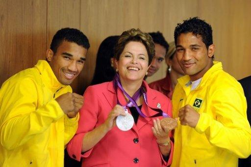 """Brazilian President Dilma Rousseff (C) poses with Olympic boxers Yamaguchi Falcao (R) and Esquiva Falcao (L) and their medals. Rousseff received the Olympic flag on Tuesday as the competition's world governing body warned that the country had to """"work harder"""" ahead of the Rio 2016 Summer Games"""