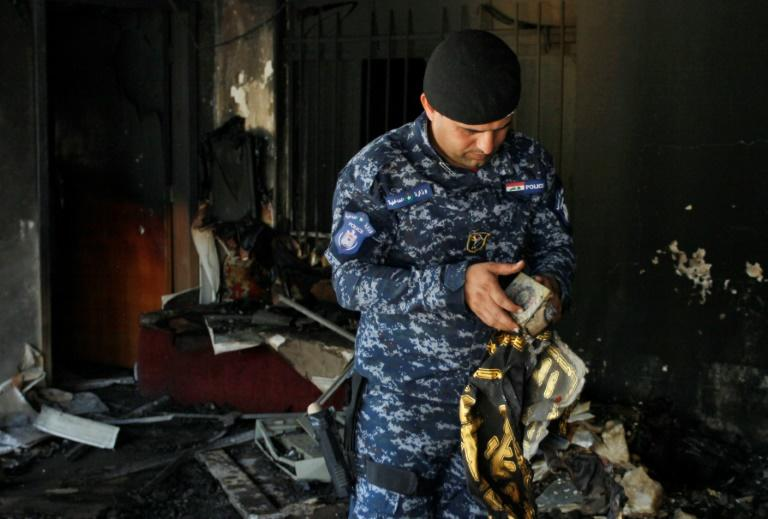 An Iraqi policeman holds a recovered holy Koran from the premises of the Islamic Dawa Party that was torched during protests in the central shrine city of Najaf on July 14, 2018