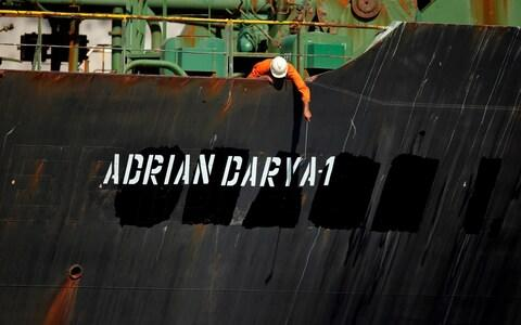 <span>A crew member looks over the side of the tanker at its new name</span> <span>Credit:  JON NAZCA/ REUTERS </span>