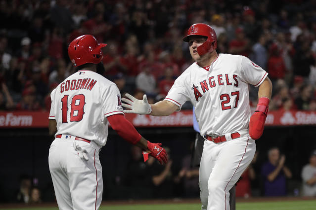 Los Angeles Angels' Mike Trout, right, is greeted by Brian Goodwin after he scored on a single by Albert Pujols during the first inning of a baseball game against the Milwaukee Brewers, Tuesday, April 9, 2019, in Anaheim, Calif. (AP Photo/Jae C. Hong)