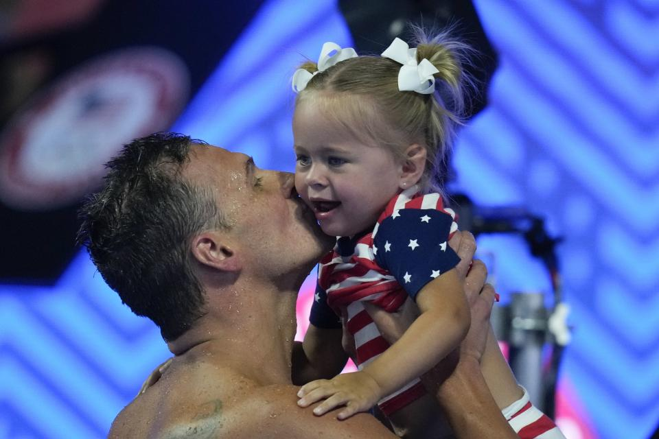 Ryan Lochte kisses his daughter after his heat in the men's 200 Individual Medley during wave 2 of the U.S. Olympic Swim Trials on Thursday, June 17, 2021, in Omaha, Neb. (AP Photo/Charlie Neibergall)