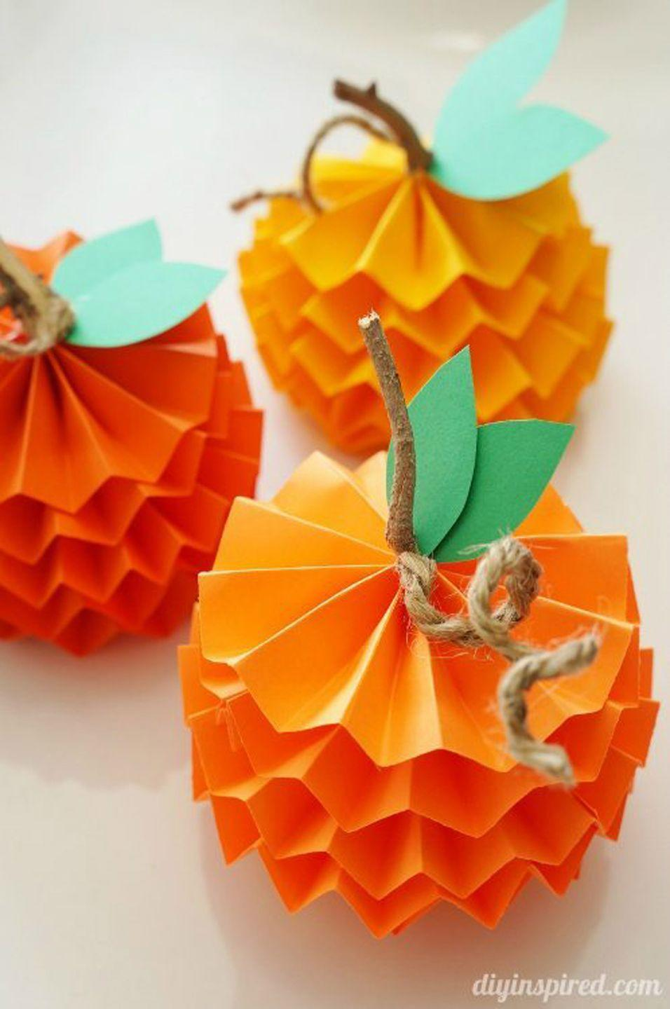 """<p>We think these paper pumpkins would look lovely on any dining table as a whimsical alternative to a typical floral centerpiece. Place them lengthwise along a burlap runner, or gather several together in a glass bowl in the middle of the table.</p><p><strong>Get the tutorial at <a href=""""https://www.diyinspired.com/how-to-make-paper-pumpkins-for-fall/"""" rel=""""nofollow noopener"""" target=""""_blank"""" data-ylk=""""slk:DIY Inspired"""" class=""""link rapid-noclick-resp"""">DIY Inspired</a>.</strong> </p>"""
