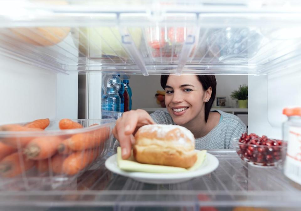 Smiling young woman having an unhealthy snack, she is taking a delicious pastry out of the fridge