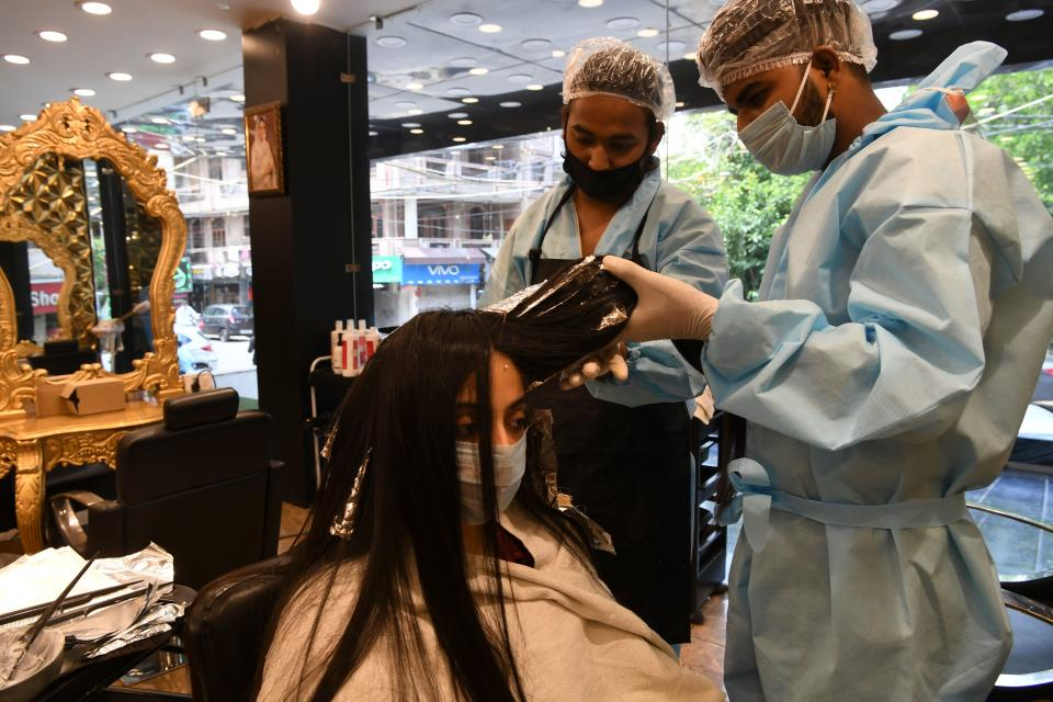 Hairdressers wearing personal protective equipment (PPE) attend a customer (C) at a hair salon, after the government eased a nationwide lockdown as a preventive measure against the COVID-19 coronavirus, in New Delhi on June 9, 2020. - India's national capital is staring at the possibility of at least half a million corona positive cases by the end of July, the deputy chief minister of Delhi told journalists on June 9. (Photo by Prakash SINGH / AFP) (Photo by PRAKASH SINGH/AFP via Getty Images)