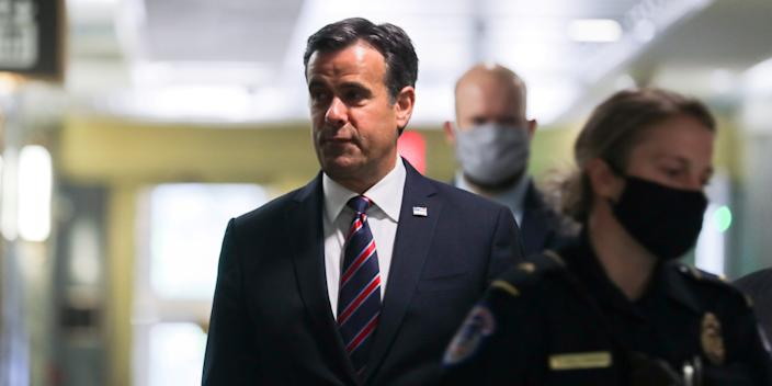 FILE PHOTO: U.S. Rep. John Ratcliffe (R-TX), President Donald Trump's nominee to be Director of National Intelligence, is escorted by U.S. Capitol police officers and other security officials wearing face masks because of the COVID-19 disease outbreak as he arrives to testify at his U.S. Senate confirmation hearing in front of the Senate Intelligence Committee in Washington, U.S. May 5, 2020. REUTERS/Carlos Barria