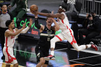 Milwaukee Bucks' Brook Lopez (11) is fouled by Houston Rockets' Danuel House Jr. during the first half of an NBA basketball game Friday, May 7, 2021, in Milwaukee. (AP Photo/Aaron Gash)