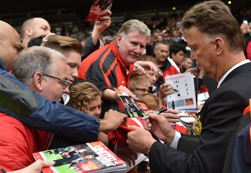 Manchester United's Dutch manager Louis van Gaal signs autographs at Old Trafford in Manchester on August 16, 2014 (AFP Photo/Paul Ellis)