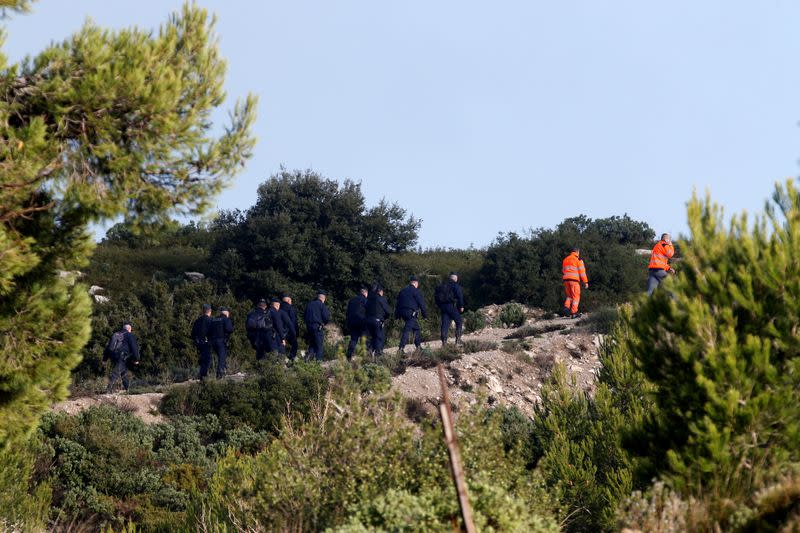 French police and emergency services work around the site where a helicopter from the civil security services crashed near Marseille
