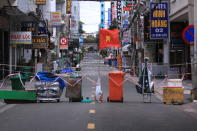 An alley is blocked with trash can and a Vietnamese flags in Vung Tau, Vietnam, Monday, Sept. 13, 2021. In Vung Tau, just outside Ho Chi Minh city, streets are sealed and checkpoints are set up to control the movement of people. Barbed wire, door panels, steel sheets, chairs and tables are among materials being used to fence up alleys and isolate neighborhoods.(AP Photo/Hau Dinh)