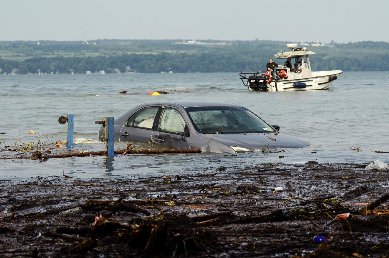 <p>A car is seen floating in Seneca Lake as crews attempt to drag a shed out of the water at Lodi Point in Lodi, N.Y., Wednesday, August 15, 2018, after heavy rain and flash flooding on August 14, 2018, led to evacuations and destruction in the Finger Lakes region. (AP Photo/Heather Ainsworth) </p>