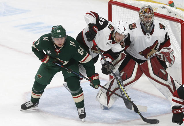 Arizona Coyotes' Jordan Oesterle, center, trips between Minnesota Wild's Mikael Granlund, left, of Finland and Coyotes goalie Antti Raanta, also of Finland, duirng the second period of an NHL hockey game Tuesday, Nov. 27, 2018, in St. Paul, Minn. (AP Photo/Jim Mone)