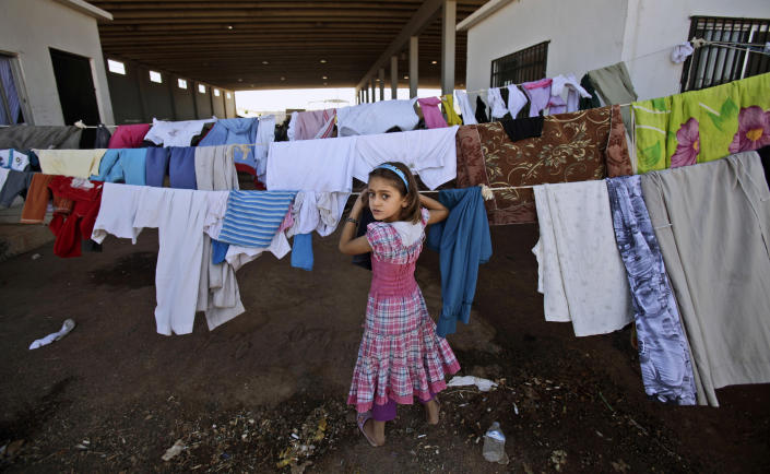 FILE - In this Sunday, Aug. 26, 2012 file photo, a Syrian girl, who fled her home with her family due to fighting between the Syrian army and the rebels, looks back while checking her laundry as she and others take refuge at the Bab Al-Salameh border crossing with Turkey, near the Syrian town of Azaz. As sectarian slayings have swelled between Syria's Sunni majority and the Alawite minority during the country's 17-month-old conflict, so has the segregation of the two communities as they flee each other. (AP Photo/Muhammed Muheisen, File)