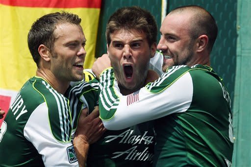Portland Timbers' David Horst, center, is hugged by Jack Jewsbury, left, and Kris Boyd, right, after scoring in the first half during an MLS soccer game with the Seattle Sounders, Sunday, June 24, 2012, in Portland, Ore. (AP Photo/Rick Bowmer)