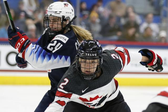 Canada's Meghan Agosta (2) defends against United States' Dani Cameranesi (24) during the first period of a rivalry series women's hockey game in Hartford, Conn., Saturday, Dec. 14, 2019. (AP Photo/Michael Dwyer)