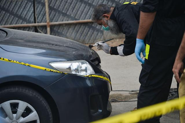 EDITORS NOTE: Graphic content / Members of Police Crime Scene Unit investigate around a car used by alleged gunmen at the main entrance of the Pakistan Stock Exchange building in Karachi on June 29, 2020. - At least six people were killed when gunmen attacked the Pakistan Stock Exchange in Karachi on June 29, with a policeman among the dead after the assailants opened fire and hurled a grenade at the trading floor, police said. (Photo by Rizwan TABASSUM / AFP) (Photo by RIZWAN TABASSUM/AFP via Getty Images)