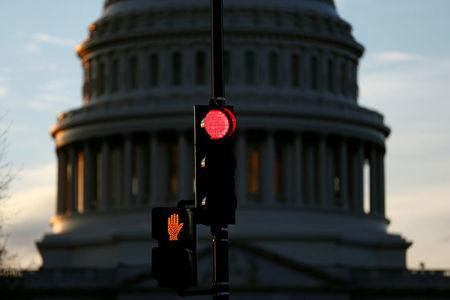A traffic light shines red after President Donald Trump and the U.S. Congress failed to reach a deal on funding for federal agencies in Washington, U.S., January 20, 2018. REUTERS/Joshua Roberts
