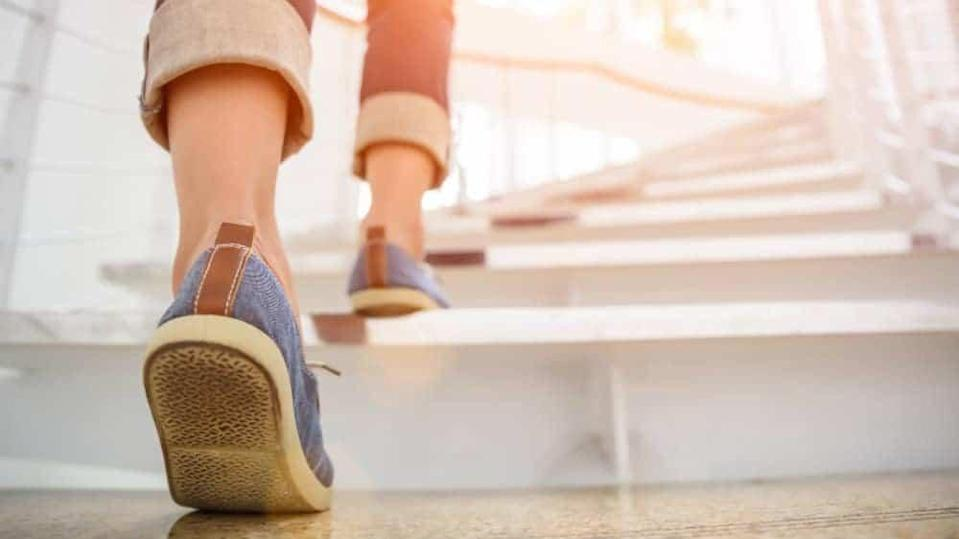 Young adult woman walking up the stairs with sun sport background