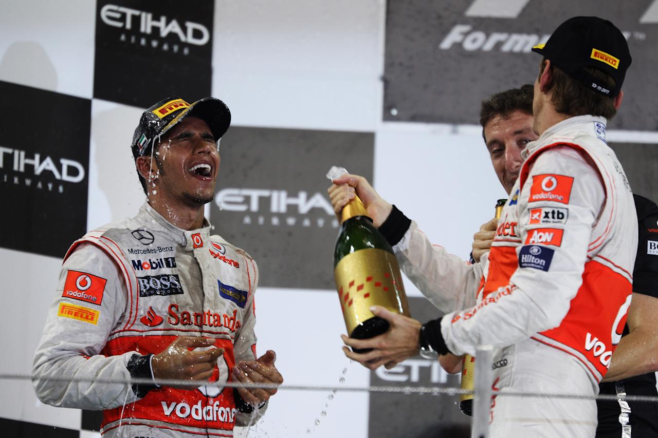 ABU DHABI, UNITED ARAB EMIRATES - NOVEMBER 13: Race winner Lewis Hamilton (L) of Great Britain and McLaren celebrates on the podium with third placed Jenson Button (R) of Great Britain and McLaren following the Abu Dhabi Formula One Grand Prix at the Yas Marina Circuit on November 13, 2011 in Abu Dhabi, United Arab Emirates. (Photo by Mark Thompson/Getty Images)