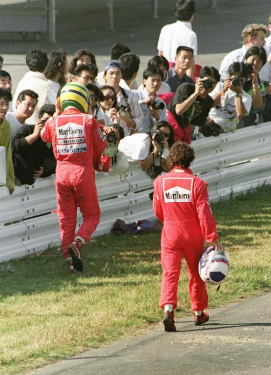 Walking but not talking: Ayrton Senna, left, and Alain Prost trudge back to the Suzuka pits after their first-turn crash in 1990