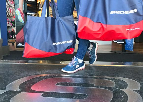 Customer carrying two Skechers bags out of the store, while wearing Skechers shoes.