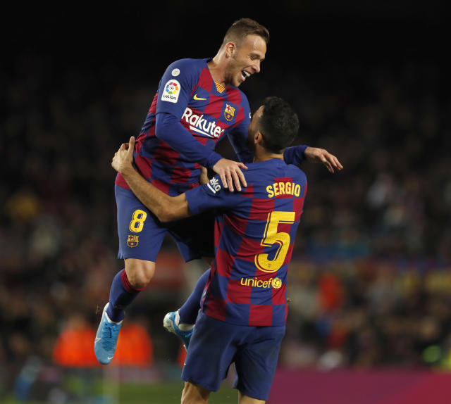 Barcelona's Arthur, left, celebrates with Barcelona's Sergio Busquets who scored his side's fourth goal during a Spanish La Liga soccer match between Barcelona and Celta at Camp Nou stadium in Barcelona, Saturday, Nov. 9, 2019. (AP Photo/Joan Monfort)