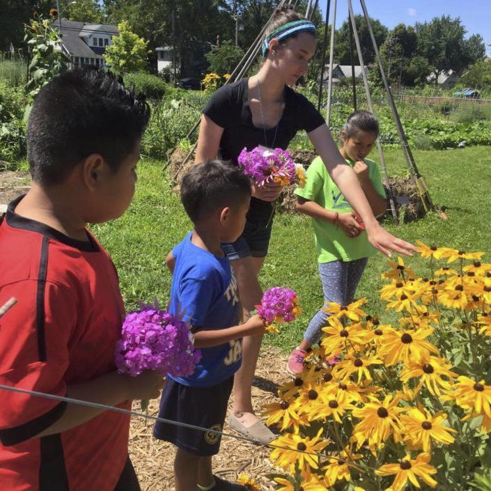 In this photo provided by Ginny Hughes, members of the Troy Kids' Garden Learning Community make bouquets at Troy Gardens in Madison, Wis. (Ginny Hughes via AP)