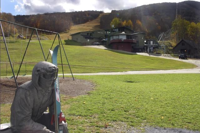 In this Oct. 23, 2019, photo, a sculpture of a skier and slopes, rear, await the ski season at Sugarbush Resort in Warren, Vt. In the tight labor market, ski areas are having a tough time hiring seasonal workers so they're upping the ante by boosting wages, offering more worker housing and other incentives. (AP Photo/Lisa Rathke)
