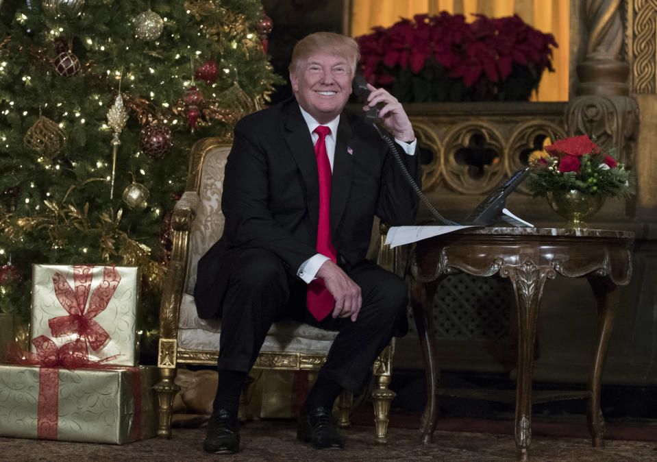 President Trump, at Mar-a-Lago on Christmas Eve, talks on the phone with children as they track Santa's movements with the North American Aerospace Defense Command (NORAD) Santa Tracker. (AP Photo/Carolyn Kaster)