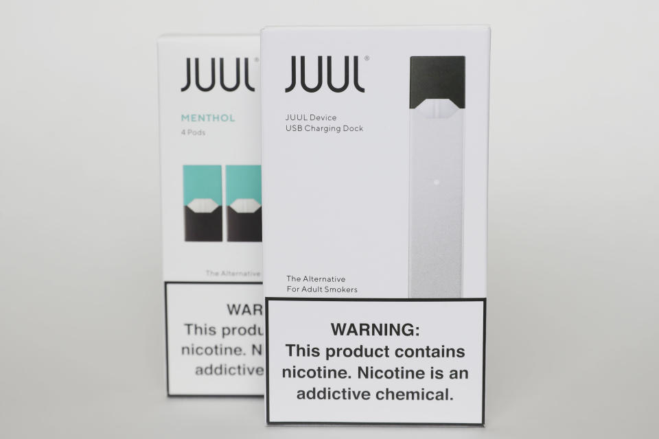 FILE - This Tuesday, Feb. 25, 2020 file photo shows packaging for an electronic cigarette and menthol pods from Juul Labs, in Pembroke Pines, Fla. Juul Labs Inc. will pay $40 million to North Carolina and take more action to prevent underage use and sales, according to a landmark legal settlement announced Monday, June 18, 2021, after years of accusations that the company had fueled an explosion in teen vaping. (AP Photo/Brynn Anderson)